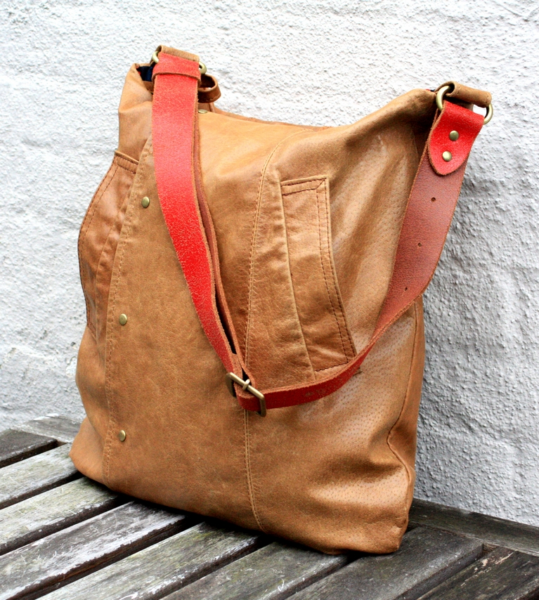 Cognac brown leather bag with a red strap